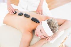 Beautiful blonde enjoying a hot stone massage stock photos