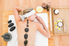 Beautiful blonde enjoying a hot stone massage Royalty Free Stock Image