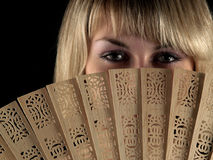 Beautiful blonde with fan. Beautiful young blonde lady with fan on black isolated Royalty Free Stock Image