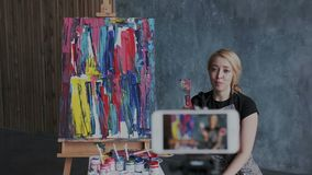 Beautiful blonde female artist recording video blog about contemporary technique of painting. She talking to followers