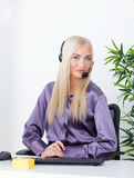 Beautiful blonde, female customer service operator using headset Royalty Free Stock Photos