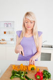 Beautiful blonde female cutting peppers Stock Images