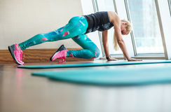 Beautiful blonde female doing fitness exercises in modern gym stock image