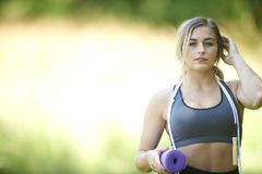 Beautiful blonde female fitness model outside in summer. Stunning young blonde woman working out in summer heat - jump rope holding yoga mat - fitness royalty free stock images