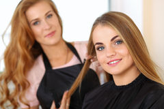 Beautiful blonde female hairdresser holding lock of hair. In hands and picking proper hairdo to smiling long haired customer. Hairdresser salon, barber shop Royalty Free Stock Photo