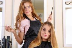 Beautiful blonde female hairdresser holding scissors Royalty Free Stock Photo