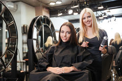 Beautiful blonde female hairdresser holding scissors and comb Stock Photography