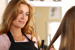Beautiful blonde female hairdresser holding scissors in hands Stock Images