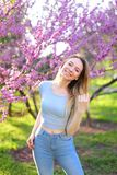 Beautiful blonde female photo model standing in park with blossom background. Beautiful blonde female person standing in garden with blossom background. Concept royalty free stock photos