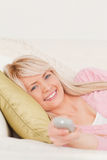Beautiful blonde female posing on a sofa Stock Image