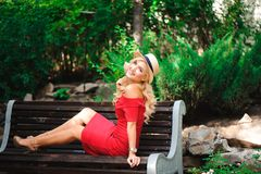 Beautiful blonde female sitting on a bench. royalty free stock image