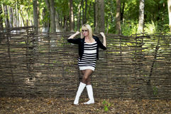 The beautiful blonde at a fence, wattled from branches Royalty Free Stock Photos