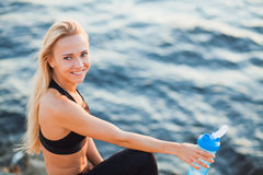 Beautiful blonde fit woman drink water on rocky beach from shaker Royalty Free Stock Images