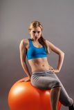 Beautiful blonde fitness woman sitting on a orange exercise ball Stock Photo