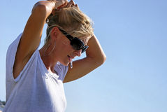 Beautiful blonde fixing hair. A beautiful blonde woman outsdie at the beach is fixing her hair, wearing sunglasses, large hoop earrrings and a shiny tee shirt Royalty Free Stock Photography