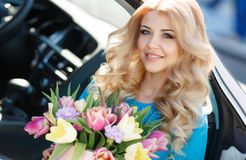 Beautiful blonde with flowers in gift box. Young beautiful woman with long blonde curly hair and gray eyes,light makeup and a beautiful smile,dressed in blue stock photos