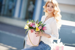 Beautiful blonde with flowers in gift box. Young beautiful woman with long blonde curly hair and gray eyes,light makeup and a beautiful smile,dressed in a white royalty free stock image