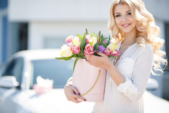 Beautiful blonde with flowers in gift box. Young beautiful woman with long blonde curly hair and gray eyes,light makeup and a beautiful smile,dressed in a white royalty free stock images