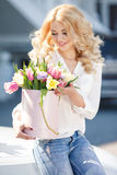 Beautiful blonde with flowers in gift box. Young beautiful woman with long blonde curly hair and gray eyes,light makeup and a beautiful smile,dressed in a white stock photo
