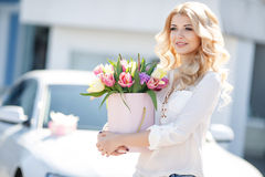 Beautiful blonde with flowers in gift box. Young beautiful woman with long blonde curly hair and gray eyes,light makeup and a beautiful smile,dressed in a white royalty free stock photos
