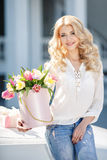 Beautiful blonde with flowers in gift box. Young beautiful woman with long blonde curly hair and gray eyes,light makeup and a beautiful smile,dressed in a white stock image
