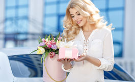 Beautiful blonde with flowers in gift box royalty free stock image