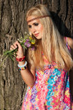 Beautiful blonde with flowers stand by tree Royalty Free Stock Image