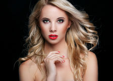 Beautiful blonde with flying hair. On a black background stock photos
