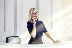 Beautiful blonde friendly woman behind the reception desk, administrator talking by phone. Sunshine in modern office. Royalty Free Stock Photos