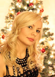 Beautiful blonde in front of christmas tree. Beautiful blonde girl in front of christmas tree royalty free stock photos