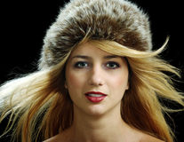 Beautiful blonde in fur hat with naked shoulders. Isolated on black Stock Images