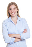 Beautiful blonde german woman in blue blouse with crossed arms Royalty Free Stock Photography