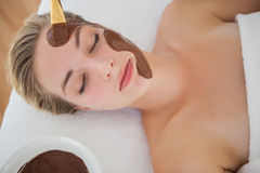 Beautiful blonde getting a chocolate facial treatment Royalty Free Stock Photography