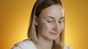 Beautiful blonde getting a facial on a yellow background stock footage