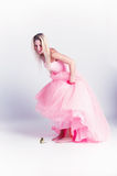 Beautiful Blonde Girl. A pretty, young, caucaian, blonde girl standing.  She's wearing a pink evening gown and is barefoot, holding up the dress in fear of a Stock Photography