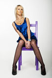 Beautiful blonde girl. Sitting on a chair Stock Photos