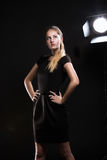 Beautiful blonde girl against light equipment at studio Royalty Free Stock Image