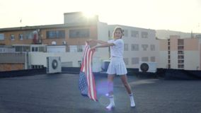 Beautiful blonde girl and american flag stock footage