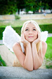 Beautiful blonde girl with angel wings. Smiling in the park royalty free stock images