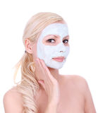 Beautiful blonde girl applying clay mask on face Stock Photos
