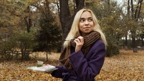 Half length portrait of young artist posing in the autumn park stock photo