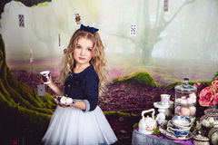 Beautiful blonde girl as Alice in Wonderland. Beautiful blonde girl in the image of Alice in Wonderland with a cup of tea and sweets in her hands stock photo