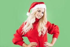 Beautiful blonde girl as a santa smiling to you. Funny scene of blonde, crazy woman wearing santa`s clothes Stock Image