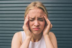 Beautiful blonde girl on the background , angry screaming woman, headache. Portrait of a stressed woman holding head in Royalty Free Stock Photo