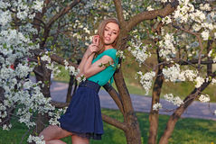 Beautiful blonde girl on the background of white flowers Stock Photo