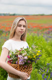 Beautiful blonde girl with basket of wildflowers Stock Photography