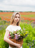 Beautiful blonde girl with basket of wildflowers Royalty Free Stock Photo