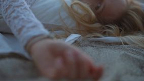 Beautiful blonde girl on the beach. Looks at the sea and the camera. shooted in golden hour. emotional face on the beach stock video