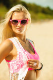 Beautiful blonde girl on beach, summertime. Holidays, vacation travel and freedom concept. Beautiful blonde tanned girl on beach. Young woman in pink sunglasses stock image