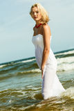 Beautiful blonde girl on beach, summertime Stock Photography
